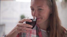 Μια νέα γυναίκα πίνει το κόκκινο ξηρό κρασί από glas απόθεμα βίντεο
