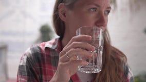 Μια νέα γυναίκα πίνει το νερό από ένα φλυτζάνι γυαλιού απόθεμα βίντεο