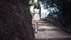 Μια νέα γυναίκα περπατά κάτω από τα σκαλοπάτια έξω σε ένα πάρκο απόθεμα βίντεο