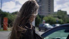Μια νέα γυναίκα πλησιάζει το αυτοκίνητό της, το οποίο οι στάσεις στο χώρο στάθμευσης, η κυρία ανοίγουν την πόρτα για να καθίσουν  απόθεμα βίντεο