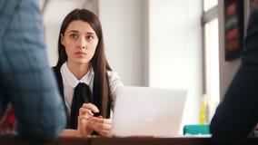 Μια νέα γυναίκα που μια έκθεση σχετικά με την εργασία της Άκουσμα τις παρατηρήσεις στην έκθεσή της φιλμ μικρού μήκους