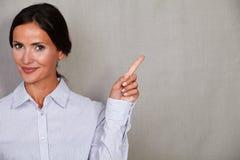 Μια νέα γυναίκα που δείχνει το αριστερό της Στοκ Εικόνες