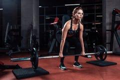 Μια νέα γυναίκα που εργάζεται σκληρά στη γυμναστική Ανυψώνει τα βάρη στοκ φωτογραφία