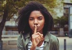 Μια νέα γυναίκα που κάνει τη χειρονομία σιωπής στοκ φωτογραφία