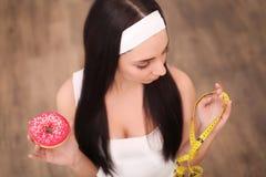 Μια νέα γυναίκα που κρατά doughnut και μια μετρώντας ταινία Ένα κορίτσι στέκεται σε ένα ξύλινο υπόβαθρο κορυφαία όψη Η έννοια του Στοκ φωτογραφίες με δικαίωμα ελεύθερης χρήσης