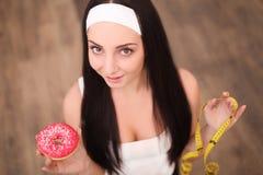 Μια νέα γυναίκα που κρατά doughnut και μια μετρώντας ταινία Ένα κορίτσι στέκεται σε ένα ξύλινο υπόβαθρο κορυφαία όψη Η έννοια του Στοκ φωτογραφία με δικαίωμα ελεύθερης χρήσης