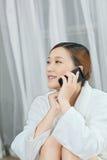 Μια νέα γυναίκα που μιλά με τηλέφωνο κυττάρων στο σαλόνι SPA Στοκ φωτογραφία με δικαίωμα ελεύθερης χρήσης
