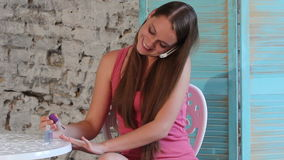 Μια νέα γυναίκα που μιλά στο τηλέφωνο και που κάνει τα καρφιά της φιλμ μικρού μήκους