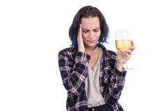 Μια νέα γυναίκα, που παρουσιάζει έναν πονοκέφαλο, και που κρατά ένα ποτήρι του κρασιού στο χέρι της Απομονωμένος στο λευκό στοκ εικόνες με δικαίωμα ελεύθερης χρήσης