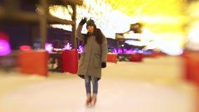 Μια νέα γυναίκα που στέκεται σε μια ανοικτή αίθουσα παγοδρομίας, που χαμογελά και που κυματίζει με το χέρι της απόθεμα βίντεο