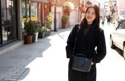 Μια νέα γυναίκα που φορά ένα μαύρο πουλόβερ στοκ εικόνες