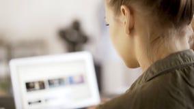 Μια νέα γυναίκα που φορά μια πράσινη δακτυλογράφηση πουκάμισων στο lap-top της σε ένα γραφείο Πέρα από τον πυροβολισμό ώμων Στοκ εικόνες με δικαίωμα ελεύθερης χρήσης