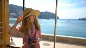 Μια νέα γυναίκα που φορά την απόλαυση καπέλων αχύρου που ταξιδεύει σε ένα παλαιό τραμ ή ένα τραίνο κατά μήκος της παραλίας απόθεμα βίντεο