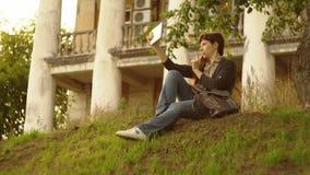 Μια νέα γυναίκα που χρησιμοποιεί μια άσπρη ψηφιακή ταμπλέτα, που κάθεται σε έναν πράσινο λόφο στο ηλιοβασίλεμα απόθεμα βίντεο