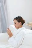 Μια νέα γυναίκα που χρησιμοποιεί ένα τηλέφωνο στο σαλόνι SPA Στοκ Φωτογραφίες