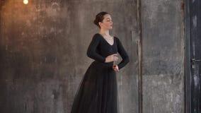 Μια νέα γυναίκα προσπαθεί να χορεψει ένα μπαλέτο, εκτελεί τις χαριτωμένες μετακινήσεις απόθεμα βίντεο
