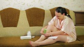 Μια νέα γυναίκα σε έναν καναπέ αφαιρεί το κερί από το δέρμα των ποδιών της με μια πετσέτα απόθεμα βίντεο