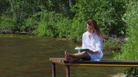 Μια νέα γυναίκα σε ένα άσπρο φόρεμα κάθεται από τον ποταμό στην αποβάθρα και διαβάζει ένα βιβλίο απόθεμα βίντεο