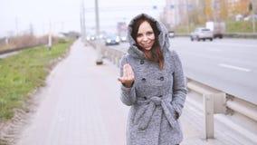 Μια νέα γυναίκα σε ένα γκρίζο παλτό φιλμ μικρού μήκους