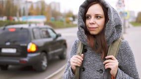 Μια νέα γυναίκα σε ένα γκρίζο παλτό απόθεμα βίντεο