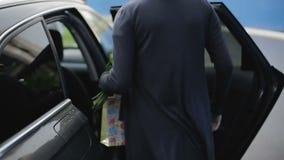 Μια νέα γυναίκα σε ένα μαύρο φόρεμα με μια ανθοδέσμη των λουλουδιών ανοίγει τη πίσω πόρτα του αυτοκινήτου και κάθεται φιλμ μικρού μήκους