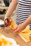 Μια νέα γυναίκα σε ένα ριγωτό πουκάμισο που κάνει ένα κίτρινο λουλούδι εγγράφου με το ψαλίδι Στοκ Εικόνες