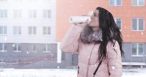 Μια νέα γυναίκα σε ένα χειμερινό παλτό πηγαίνει και πίνει το τσάι από μια θερμο κούπα φιλμ μικρού μήκους