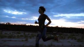 Μια νέα γυναίκα σε μια φόρμα γυμναστικής που κατά μήκος της αποβάθρας άμμου του λιμένα φορτίου, στο λυκόφως της αυγής πρωινού Όψη φιλμ μικρού μήκους