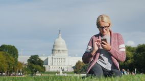 Μια νέα γυναίκα στα γυαλιά κάθεται στο χορτοτάπητα, απολαμβάνει ένα smartphone Ενάντια στο σκηνικό του Capitol στην Ουάσιγκτον, σ απόθεμα βίντεο