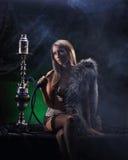 Μια νέα γυναίκα στα ερωτικά ενδύματα που καπνίζουν ένα hookah Στοκ φωτογραφία με δικαίωμα ελεύθερης χρήσης