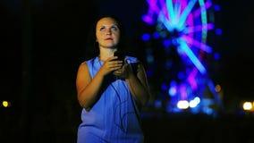Μια νέα γυναίκα στην αποβάθρα στα ακουστικά γράφει ένα μήνυμα στο τηλέφωνο ενάντια στο σκηνικό μιας καμμένος ρόδας Ferris φιλμ μικρού μήκους