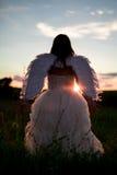 Μια νέα γυναίκα στην εικόνα του αγγέλου στέκεται σε έναν λόφο με τα αυξημένα χέρια Στοκ φωτογραφία με δικαίωμα ελεύθερης χρήσης