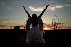 Μια νέα γυναίκα στην εικόνα του αγγέλου στέκεται σε έναν λόφο με τα αυξημένα χέρια Στοκ Εικόνες