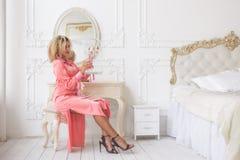 Μια νέα γυναίκα στην κρεβατοκάμαρα με το διακοσμητικό κλουβί για το πουλί στοκ εικόνες με δικαίωμα ελεύθερης χρήσης