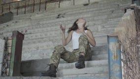Μια νέα γυναίκα στη συνεδρίαση στρατιωτικών στολών στα κρύα συγκεκριμένα σκαλοπάτια στο εγκαταλειμμένο κτήριο Στρατιώτης γυναικών απόθεμα βίντεο