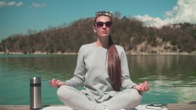 Μια νέα γυναίκα στον ήλιο καθμένος σε μια ξύλινη αποβάθρα μιας λίμνης μια ημέρα άνοιξη, που χαλαρώνει στη φύση φιλμ μικρού μήκους