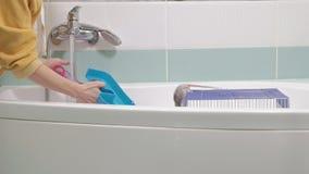 Μια νέα γυναίκα φροντίζει ένα κατοικίδιο ζώο, πλένει έναν λαβύρινθο κάτω από μια βρύση με το νερό και καθαρίζει ένα κλουβί στο λο φιλμ μικρού μήκους