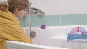 Μια νέα γυναίκα φροντίζει ένα κατοικίδιο ζώο, πλένει τα κύπελλα τροφίμων κάτω από τη βρύση με το νερό και καθαρίζει το κλουβί στο απόθεμα βίντεο