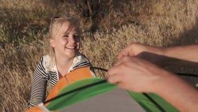 Μια νέα γυναίκα χαμογελά και μιλά, ενώ ένας νεαρός άνδρας θέτει μια σκηνή απόθεμα βίντεο