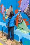 Μια νέα γυναίκα χρωματίζει μια εικόνα με έναν ψεκασμό χρώματος σε έναν συγκεκριμένο φράκτη ασφαλείας στα σύνορα μεταξύ του Ισραήλ στοκ φωτογραφίες