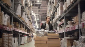 Μια νέα γυναίκα brunette που ωθεί ένα καροτσάκι με τα μέρη των κιβωτίων μεταξύ των ραφιών με τα αγαθά σε μια αποθήκη εμπορευμάτων απόθεμα βίντεο