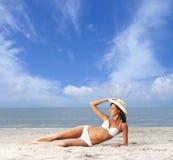 Μια νέα γυναίκα brunette σε ένα άσπρο μαγιό στην παραλία Στοκ Φωτογραφία