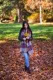 Μια νέα γυναίκα brunette σε ένα πάρκο που περιβάλλεται από την πτώση φεύγει στοκ εικόνες