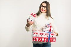 Μια νέα γυναίκα brunette στα γυαλιά και χριστουγεννιάτικα δώρα μιας τα άσπρα πουλόβερ εκμετάλλευσης στο άσπρο υπόβαθρο Χλεύη επάν Στοκ Φωτογραφία