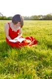 Μια νέα γυναικεία ανάγνωση στη φύση Στοκ φωτογραφία με δικαίωμα ελεύθερης χρήσης