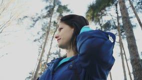 Μια νέα ελκυστική γυναίκα σε ένα πάρκο χαμογελά και παίζει με την τρίχα της, 4k απόθεμα βίντεο