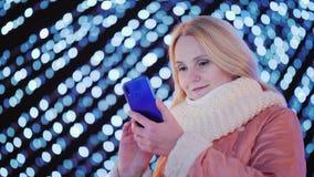 Μια νέα ελκυστική γυναίκα χρησιμοποιεί ένα smartphone στο υπόβαθρο των εορταστικών γιρλαντών στην πόλη στοκ εικόνες