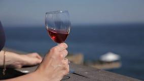 Μια νέα και ελκυστική γυναίκα πίνει το κόκκινο κρασί από goblet γυαλιού και εξετάζει τη θάλασσα, μια κυρία στην ενδυμασία βραδιού απόθεμα βίντεο