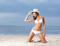 Μια νέα γυναίκα brunette σε ένα άσπρο μαγιό στην παραλία Στοκ Εικόνες