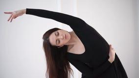 Μια νέα και όμορφη γυναίκα κάνει τις κλίσεις στην πλευρά, ζυμώνει απόθεμα βίντεο